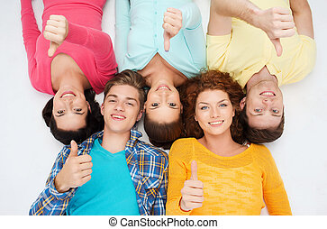 group of smiling teenagers showing thumbs up - friendship,...