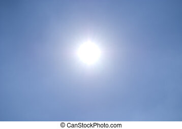 Shining sun in a clear blue sky - A shining sun/ star on a...