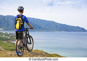 young man standing on the mountain with bike