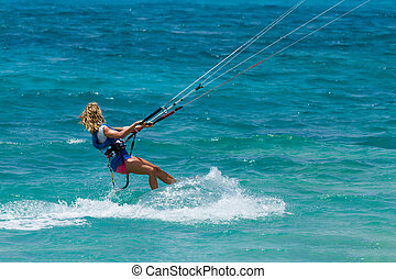 A young woman kite-surfer rides in greenish-blue sea under...
