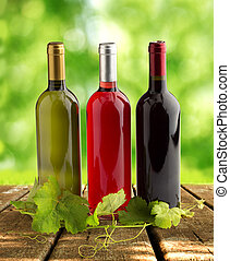 italian winery - wine bottles and grapevine on wooden table