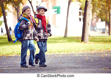 Pupils going to school - Portrait of happy twin schoolboys...