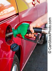 Person refueling a car at gas station - Person refueling a...