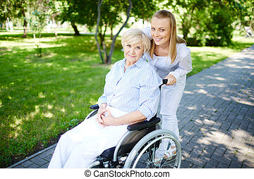 Walking out - Female caregiver walking with senior patient...
