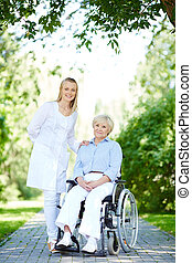 Walk with patient - Pretty nurse taking care of senior...