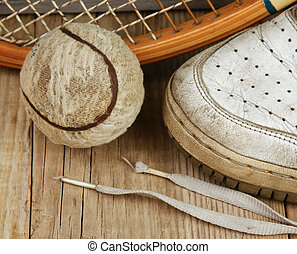 old tennis ball and sneakers on a wooden floor - old tennis...