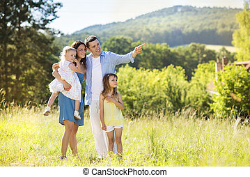 Happy family in nature - Portrait of young happy ypung...