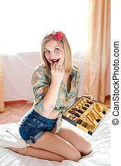 beautiful blond young woman pinup girl eating chocolate...