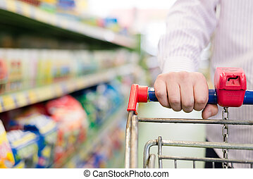 closeup on man or woman in shop with shopping trolley or...