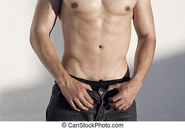 Sexy torso of young adult man wit natural sunset light