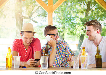 Friends drinking and using smartphone