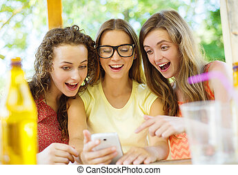 Girls having fun with smartphone in pub - Three beautiful...