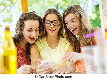 Girls having fun with smartphone in pub - Three beautiful...