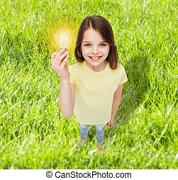 smiling little girl holding light bulb - electricity,...