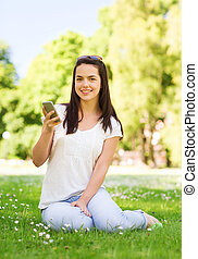 smiling young girl with smartphone sitting in park