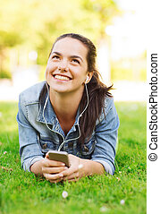 smiling young girl with smartphone and earphones -...