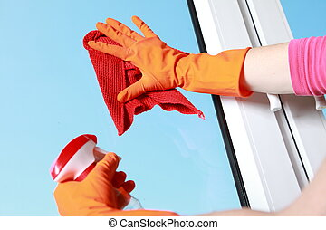 Gloved hand cleaning window rag and spray - hand in orange...