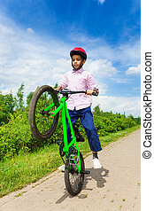 African boy with one wheel of bike up rides it - African boy...