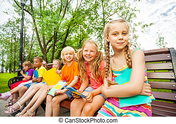 Cute children with notebooks sit on bench and have fun...