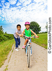 Boy helps girl to ride bike and holds handle-bar - Boy helps...