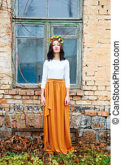 Beautiful young girl with flower wreath on her head near wooden window of an old brick building