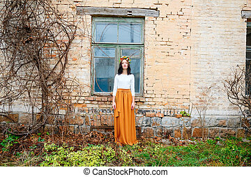Beautiful young woman with flower wreath on her head near wooden window of an old brick building