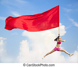 Beautiful Asian female jumping with big red flag with blue...