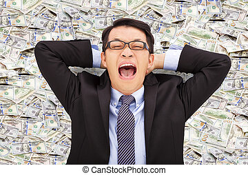 happy young business man lying on the us dollar
