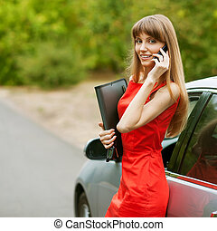 Elegant business lady in a red dress standing in front of...
