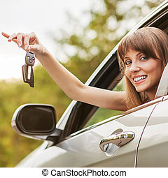 Caucasian car driver woman smiling showing new car keys and...
