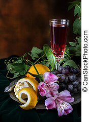Still life in antique style with a glass of wine, grapes and...