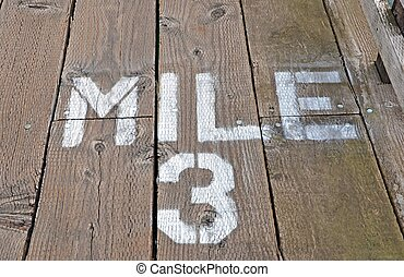 Mile 3 Painted On Boardwalk - Painted wood mile marker