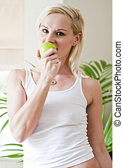 Young beautiful woman eating green apple