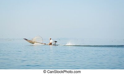 local fisherman on fishing boat with a motor Inle lake,...