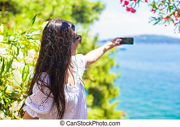 Back view of tourist woman taking photo with phone on...