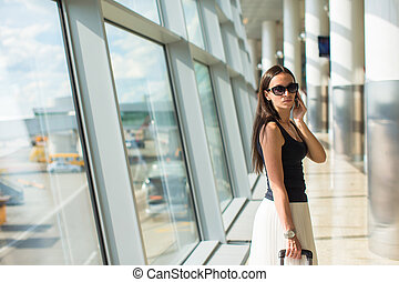Young businesswoman talking on the phone in airport