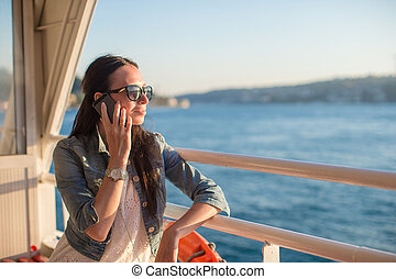 Young beautiful woman talking on her phone on summer...