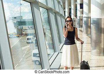 Smiling businesswoman talking on the phone in airport