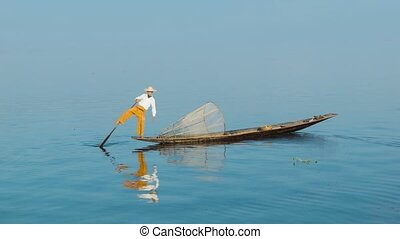 Fisherman turns a boat using paddles and feet. Inle lake,...