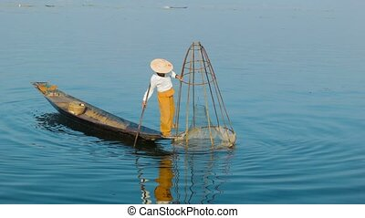 Burmese fisherman shows fish in the traditional trap. Inle...