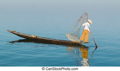 Burmese fisherman with a traditional trap on wooden boat. Inle lake, Myanmar