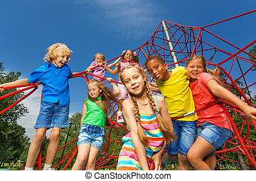 Many kids stand on red ropes together in park - Many...