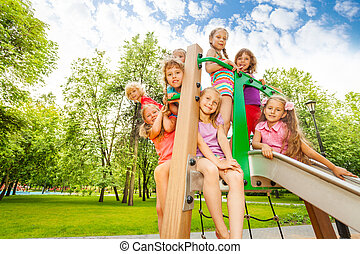 Happy kids on playground chute in the park