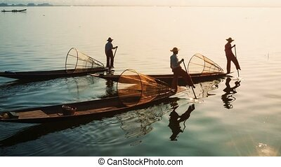 Myanmar, Inle Lake. Fishermen on vintage boats sail home with a catch