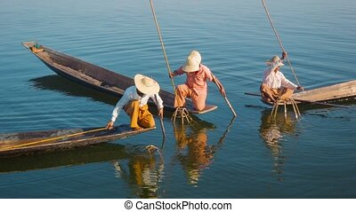 Myanmar, Inle Lake. Fishermen on boats demonstrate ancient way of fishing
