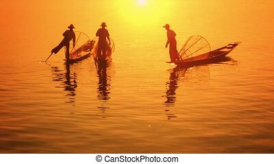 Myanmar, Inle Lake. Fishermen on vintage boats moved with legs
