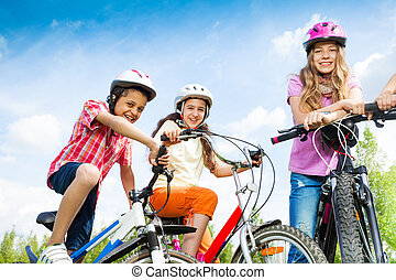 Laughing kids in helmets hold bike handle-bars - Three...