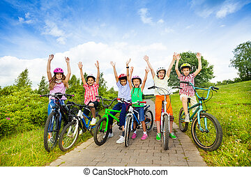 Excited kids in helmets on bikes with hands up - Excited...