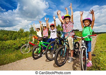 Children with helmets sit on their bikes in a row - Excited...