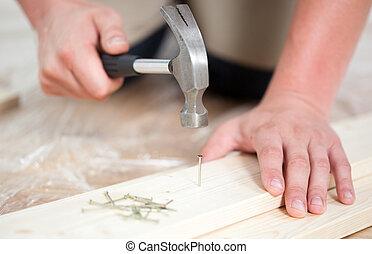 Man driving a nail during renovation, horizontal